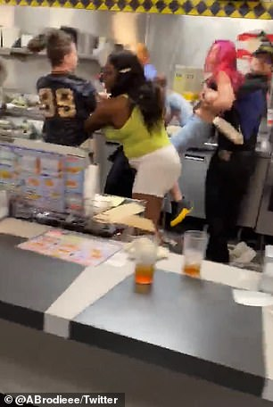 During the fight, the red-haired customer is picked up off her feet by a worker