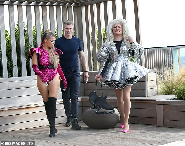 Standing out: The drag queen added a pop of colour to her appearance with her choice of footwear as she sported a pair of hot pink heels
