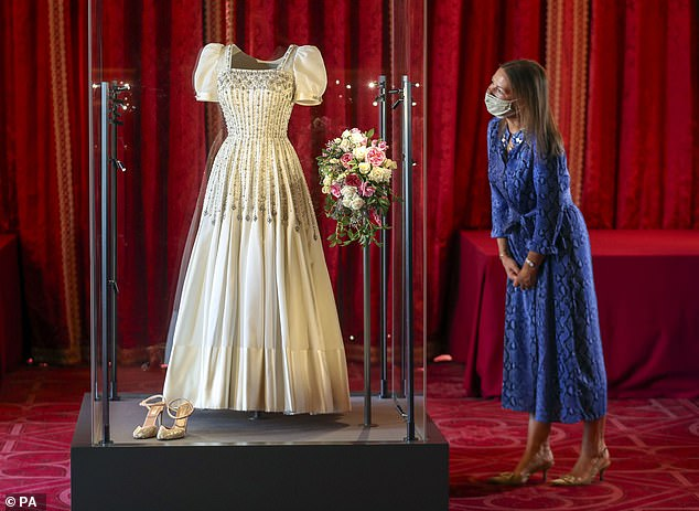 TheSir Norman Hartnell dress worn by Princess Beatrice at her scaled down wedding two months ago will be on display at Windsor Castle from Thursday. It was first worn by the Queen in the 1960s. Pictured: Royal Collection Trust curator Caroline de Guitut looks at the dress in its temporary new home
