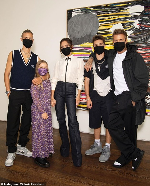 Sweet: The designer shared snaps of her husband David, sons Romeo, 18, and Cruz, 15, and daughter Harper, nine, wearing their masks ahead of the digital presentation