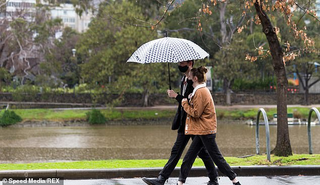 Melbourne will cop a bucketing on Friday with up to 20mm rain forecast. Pictured is a man and woman trying to keep dry on the daily wall in Melbourne last month