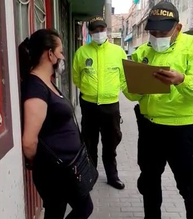 Silvia Yaney Castañeda (left) is interrogated by cops in Bogotá, Colombia, moments after she and three members of a sex trafficking ring were arrested Sunday
