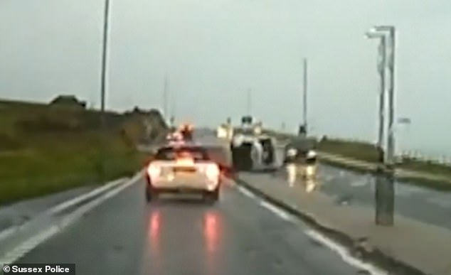 The mini breaks hard as the silver people-carrier flips onto its side after hitting the road signs on the island