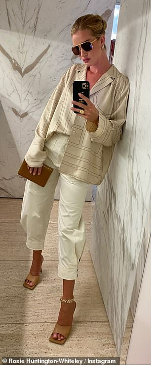 So chic: She then slippedinto a loose-fitting shirt and cropped white trousers