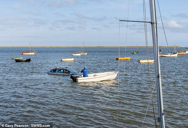 The unsuspecting driver had parked the car on a riverside road in Norfolk on Sunday - seemingly unaware that high spring tide would soon render the area more suitable for boats than for vehicles