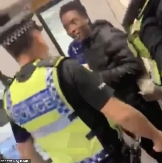 At the start of the footage, the officer can be heard repeatedly asking a passenger to put on his mask, threatening to remove him from the London Overground train if he does not.  Passenger replies: 'You have to train me, man'