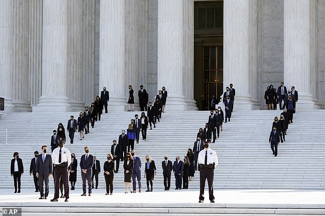 Her former law clerks - 120 in total - await the casket of Justice Ruth Bader Ginsburg to arrive at the Supreme Court