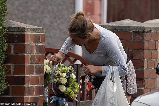 A mourner places flowers on the gate of the family home inDoncaster, South Yorkshire