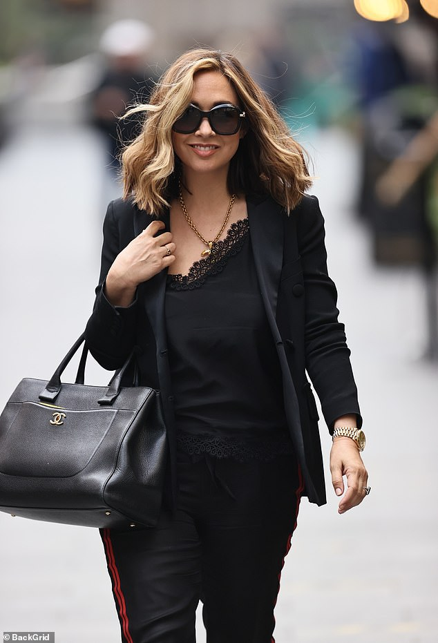 Lovely:The presenter looked chic in a black lace camisole and joggers as she strolled into Global Studios in London