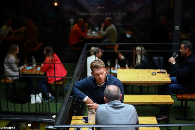 People sit in a pub in London Bridge despite the fact pubs and restaurants in England will be closed by 10pm - after Mr Johnson announced the new curfew on Tuesday
