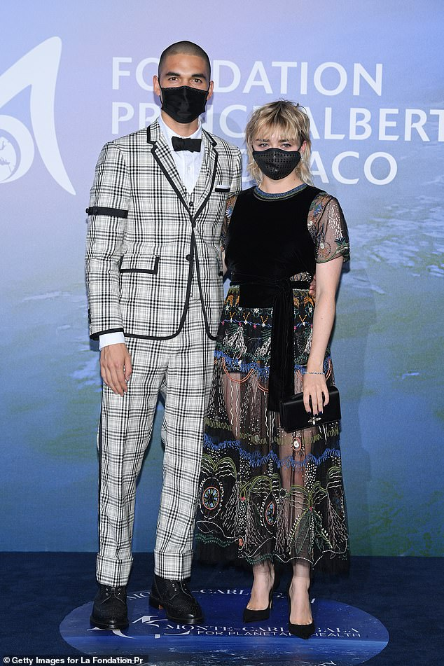 Together:Sporting a matching face mask, Maisie cosied up to her hunky beau Reuben - who she's been dating since last year - in a sharp black and white checked suit