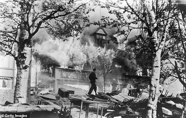 June 1940: A man runs through wreckage in front of a large house in flames, after Luftwaffe air raids secured the Nazi occupation of Norway. Narvik, Norway, World War II