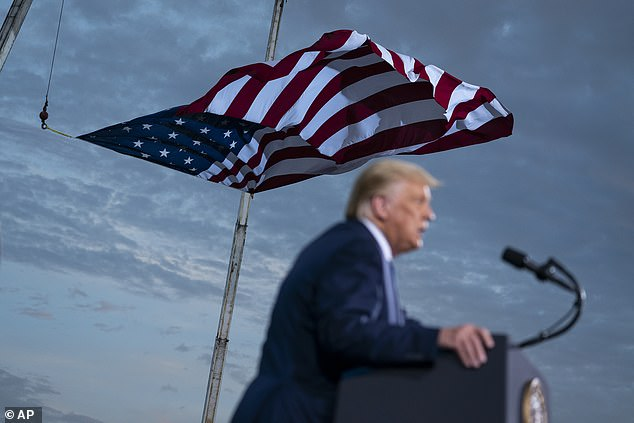 Trump, photographed with an American flag above him, mocked Biden for saying that the Black Lives Matter protests have been peaceful. 'Joe, they're not peaceful!' Trump yelled