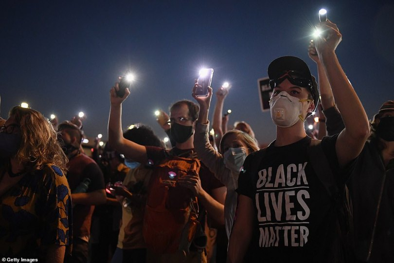 Protesters light up their cell phones during a protest action on Interstate 64 on Thursday evening