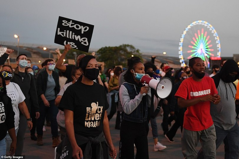 A protester holds a sign that reads 'Stop killing us' as other demonstrators take to the streets in St. Louis on Thursday