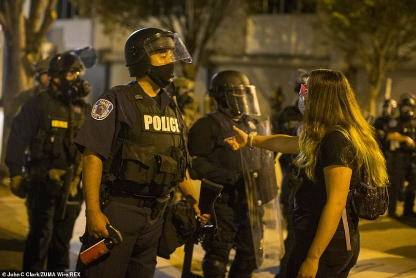 A Richmond, Virginia, police officer has pepper spray in hand while speaking to a protester at the Richmond Police Headquarters on Wednesday. Protesters gathered after a Louisville grand jury announced there would be no murder charges against the police officers who fatally shot Breonna Taylor