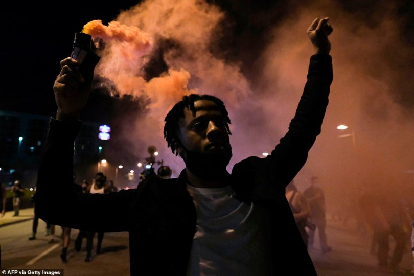 A demonstrator holds a smoke bomb as he marches to protest the lack of criminal charges in the police killing of Breonna Taylor, in downtown Louisville, Kentucky last night
