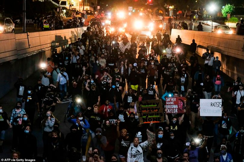 Protestors march as they protest the lack of criminal charges in the police killing of Breonna Taylor, in downtown Louisville, Kentucky last night
