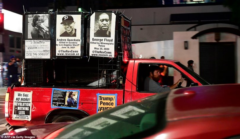 A driver in a vehicle joining protesters displays photos of Breonna Taylor, Andres Guardado and George Floyd, all killed by law enforcement personel, along Sunset Boulevard in Hollywood, California last night
