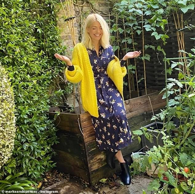 Autumn:The TV star also looked a ray of sunshine despite a downpour as she posed in the rain in a stunning chunky turmeric knit paired with a navy printed shirt dress