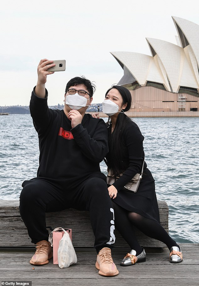The only confirmed case of the virus was from a returned traveler currently in hotel quarantine (pictured, a couple wearing face masks pose for a photo)