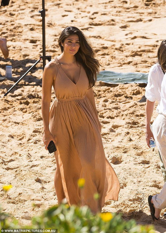 Stunning: Pia had all eyes on her as she posed for a series of photos in a long beige flowy dress on the sand
