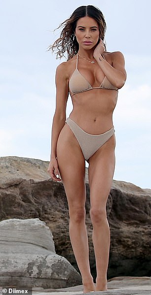 Pose: The 32-year-old looked toned and tanned as she showed off her taut physique in the nude-toned swimwear.