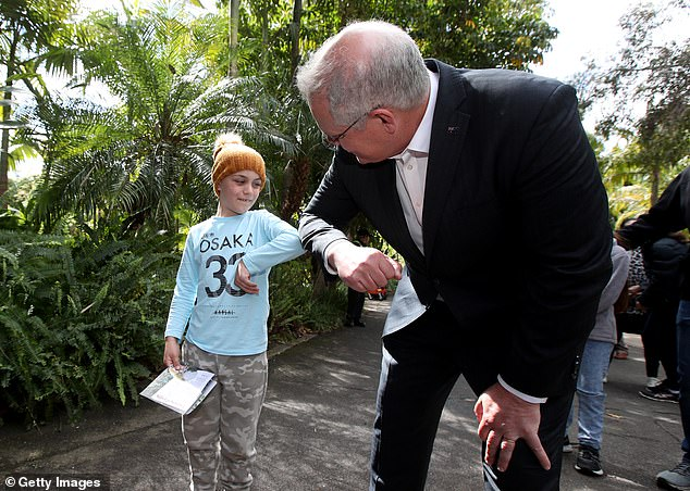 Mr Morrison bumps elbows with Adelaide zoo visitor Max wishing him a happy 7th birthday