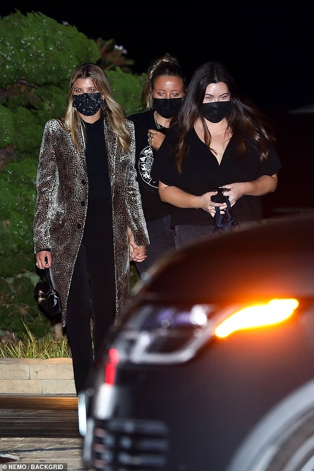 Girls' night out: The model and her friend held hands as they made their way to the taxi