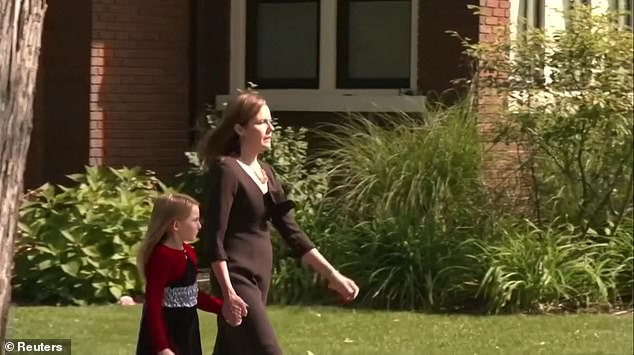 Barret held one of her daughter's hands as she walked toward their car