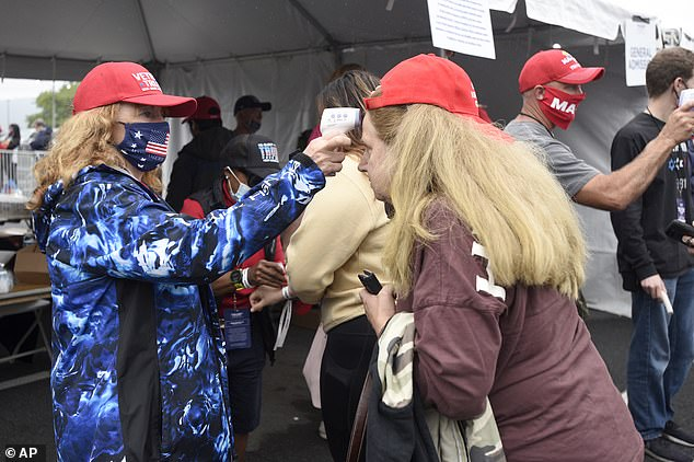 Volunteer Terri Hinckley, left, of Loganville, Pennsylvania, takes the temperatures of attendees before a campaign rally for President Donald Trump on Saturday