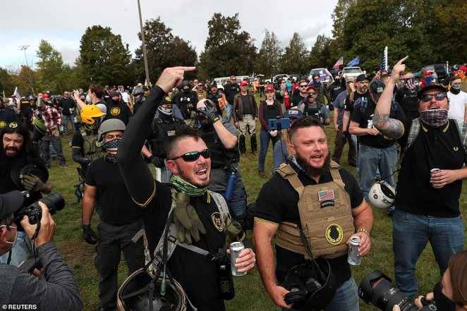 Proud Boys members drink Coors light while shouting and gesturing at the rally Saturday