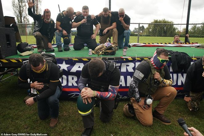 The Proud Boys bow their heads and kneel in prayer at the start of the rally which then erupted into chants