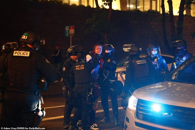 A man is arrested by Portland police during a Black Lives Matter protest on Saturday night