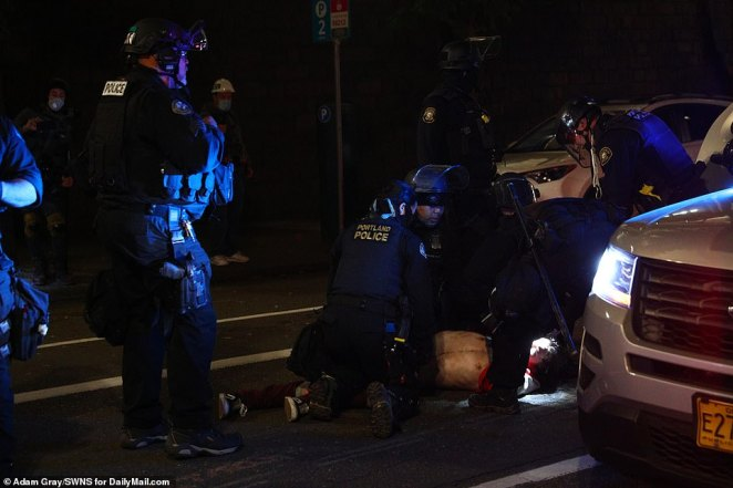 One man was forced to the floor as he was arrested by police in Portland