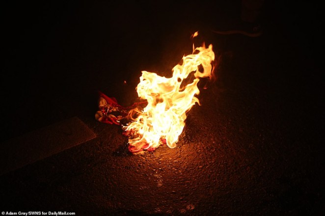 The stars and stripes were burned in the middle of the street during the protest