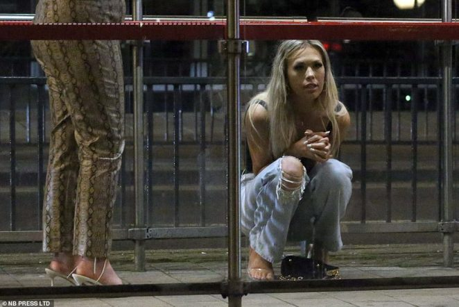 This woman sits and waits of the last bus of the night after enjoying a night out on the town in Leeds city centre