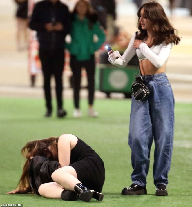 Awoman takes a photo of her companion who was seen curled up on the floor after a night out in Leeds city centre