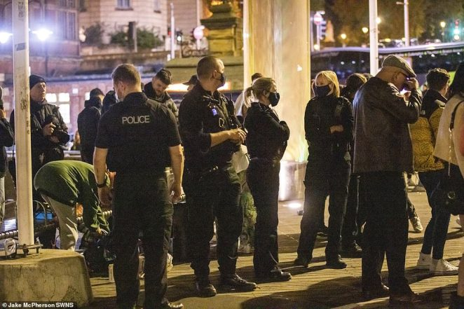 Police officers work to disperse large groups of people gathered near the Harbourside in Bristol drinking and dancing