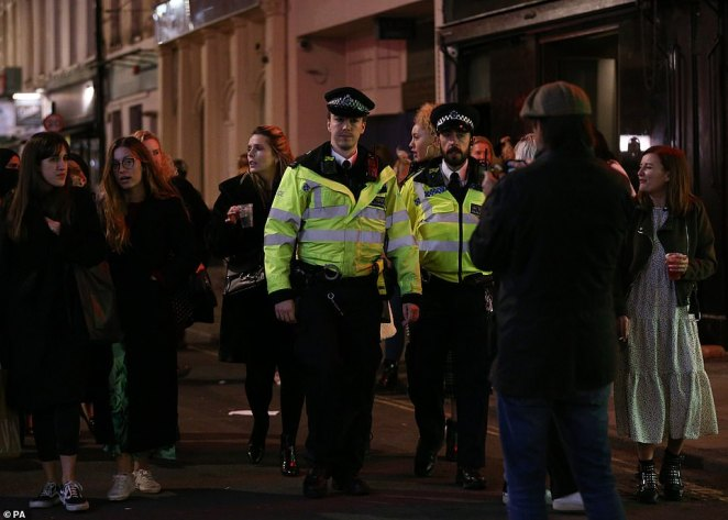 Police officers faced large crowds while on patrol at closing time in Soho, London, when the 10pm curfew came into force