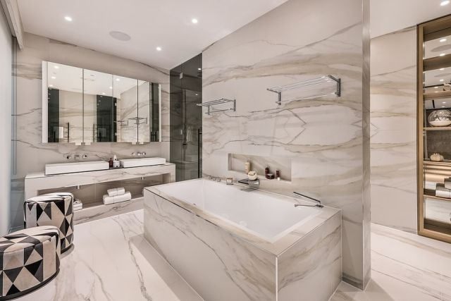 The marble clad main bathroom features modern decor, his and hers sinks and built in spotlights