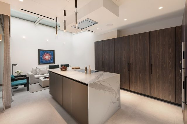 The open plan family kitchen and breakfast area features modern wooden decor, a central island boasting a chic marble design and state-of-the-art integrated appliances
