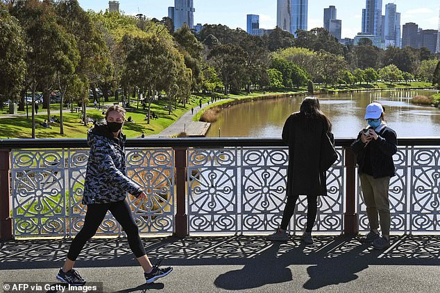 People walking on the banks of Melbourne's Yarra River on Sunday. Residents will be relieved by the end of the curfew and the lifting of many restrictions on Monday
