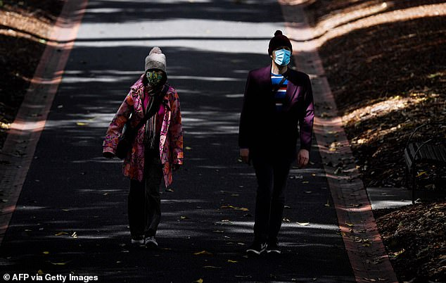 Two walkers wearing face masks wander through Treasury Gardens in Melbourne on Saturday