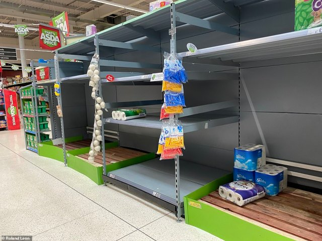 Empty shelves littered with a few rolls of toilet paper in the Asda Superstore in Barnes Hill, Birmingham