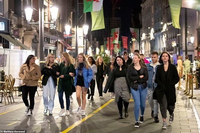 Crowds of people walk down St Mary Street in Cardiff, Wales after the pubs close at 10pm on September 26