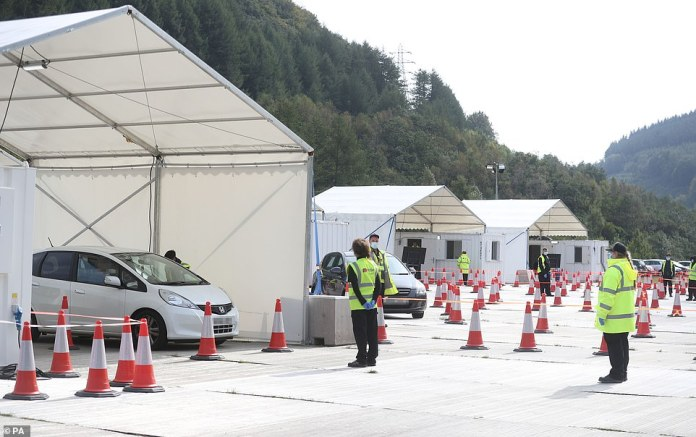 It comes as 60% of the Welsh population faces a local lockdown from tomorrow after three more council areas are added to the government's list. Pictured: Cars at a drive-through coronavirus testing station in Ebbw Vale in Wales