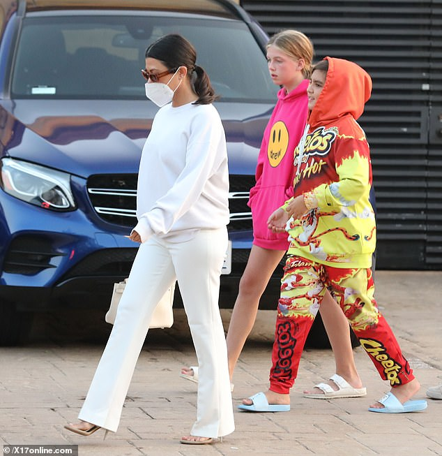 Staying safe: As they exited the restaurant, the mother-of-three chatted away with her son's friends, while sporting a white CDC-recommended face mask