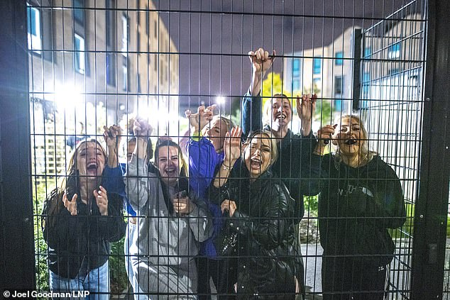 First year students at Manchester Metropolitan University (MMU) stand behind a fence after undergraduates self-isolating for a fortnight were told they cannot leave the campus