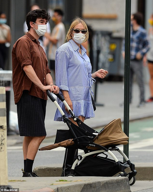 New parents: Ma¿kovi¿ opted for a baggy dark red pinstripe shirt and black shorts and also wore a mask